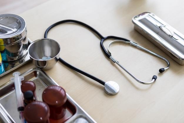 Verschiedene drogen des stethoskops, der phiole, der spritze und der medizinischen flasche auf chirurgischem behälter mit medizinischer ausrüstung auf holz