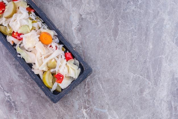 Verschiedene eingelegte gemüse auf einem brett, auf dem marmor.