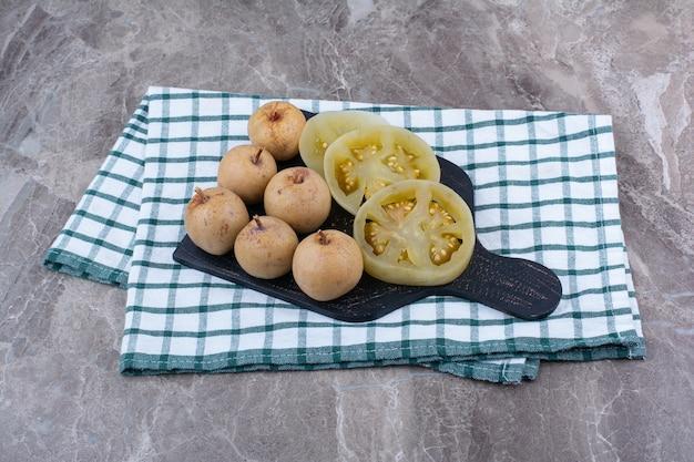 Verschiedene eingelegte gemüse und früchte auf dunklem brett.