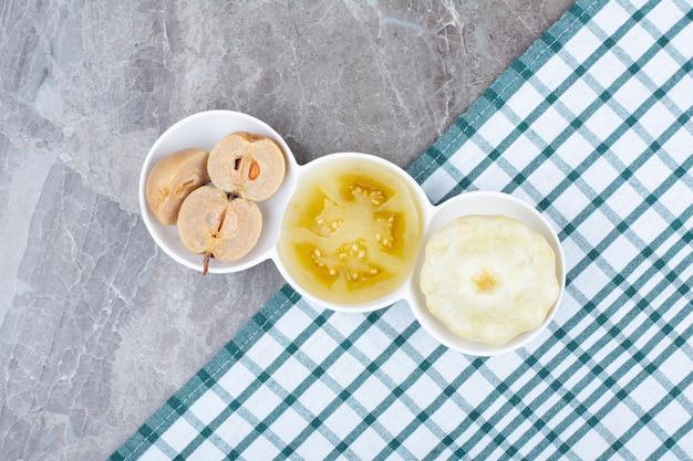 Verschiedene eingelegte gemüse und früchte in schalen mit tischdecke. hochwertiges foto