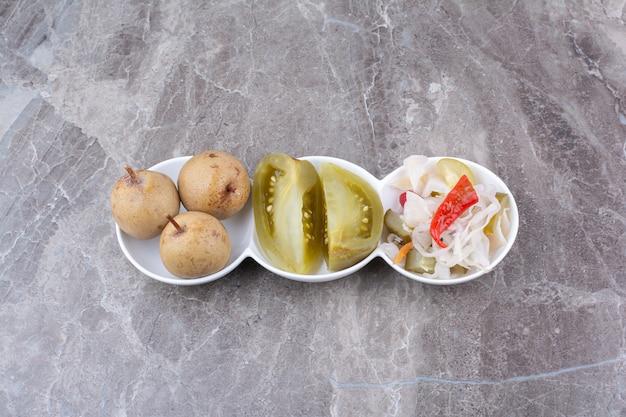 Verschiedene eingelegte gemüse und früchte in schalen.