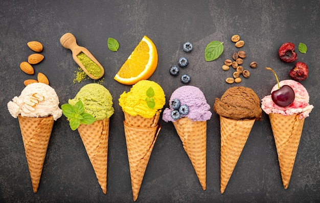 Verschiedene eiscremearomen in zapfen heidelbeeren, grünem tee, pistazien, mandeln, orangen und kirschen auf dunklem stein