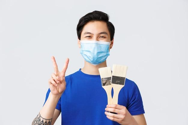 Verschiedene emotionen, lebensstil und freizeit während des coronavirus, covid-19-konzept. glücklicher asiatischer mann fand hobby in selbstquarantäne und zeigte zwei pinsel, malte und machte friedenszeichen, trug eine medizinische maske