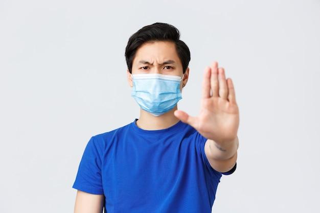 Verschiedene emotionen, lebensstil und freizeit während des coronavirus, covid-19-konzept. wütender und unzufriedener asiatischer mann in medizinischer maske sagt, er solle mit gestreckter hand aufhören, warnen oder etwas verbieten.