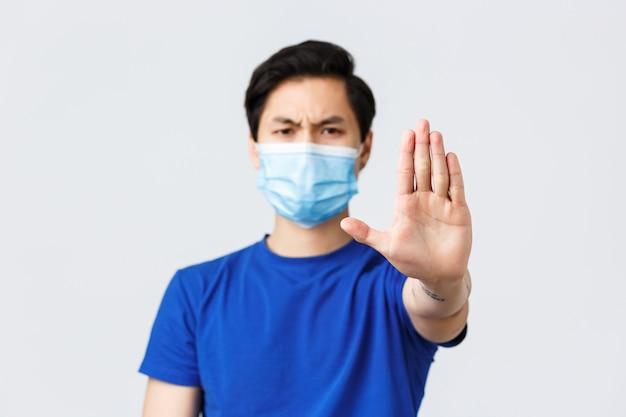 Verschiedene emotionen, lebensstil und freizeit während des coronavirus, covid-19-konzept. zeit genug aufzuhören. ernster und unzufriedener, stirnrunzelnder asiatischer mann in medizinischer maske zeigt handwarnung, verbot
