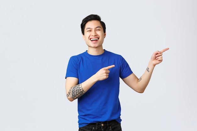 Verschiedene emotionen, lebensstil und werbekonzept der menschen. attraktiver fröhlicher queerer asiatischer mann, der den stolzmonat feiert und mit den fingern direkt auf das banner zeigt. lächelnder typ stellt produkt vor oder empfiehlt produkt