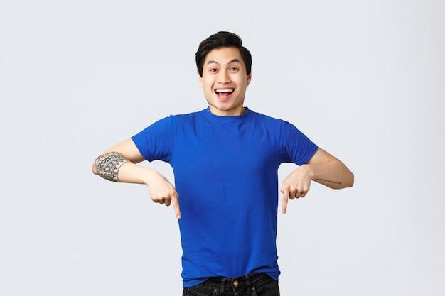 Verschiedene emotionen, lebensstil und werbekonzept der menschen. begeisterter, gutaussehender asiatischer mann im blauen t-shirt, der mit den fingern nach unten zeigt und lächelt, als gute nachrichten verkünden, grauer hintergrund.