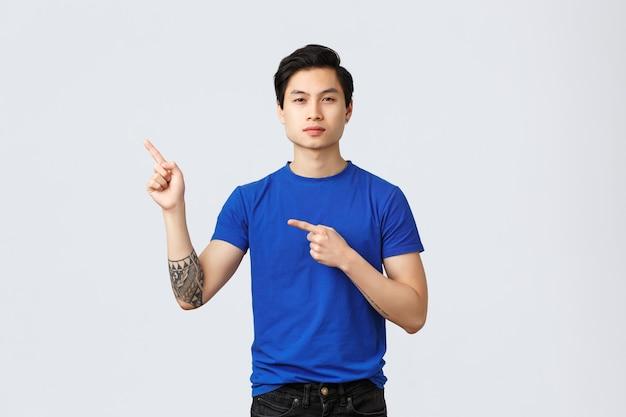 Verschiedene emotionen, lebensstil und werbekonzept der menschen. entschlossener ernsthafter asiatischer mann im blauen t-shirt, der mit den fingern auf die obere linke ecke zeigt, ein banner zeigt, ein produkt oder eine dienstleistung empfiehlt.
