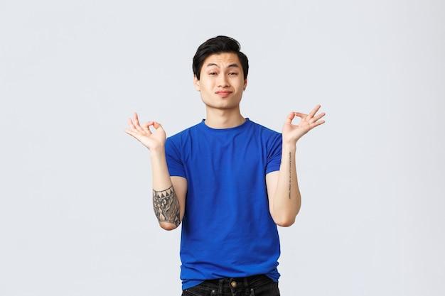 Verschiedene emotionen, lebensstil und werbekonzept der menschen. frecher gutaussehender queerer kerl, schwuler asiatischer mann im blauen t-shirt bleiben sie ruhig und geduldig, halten sie die hände, zen-meditationspose, grauer hintergrund