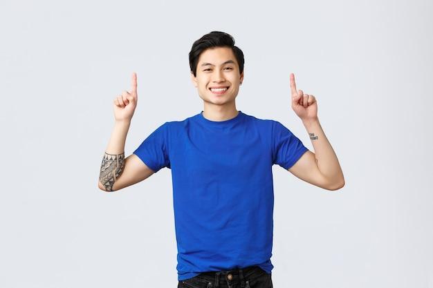 Verschiedene emotionen, lebensstil und werbekonzept der menschen. fröhlicher gutaussehender asiatischer mann im blauen t-shirt, das mit den fingern nach oben zeigt. guy werbung und informieren über neue promo, lächelnde kamera.