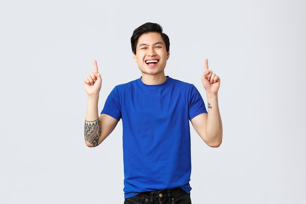 Verschiedene emotionen, lebensstil und werbekonzept der menschen. hübscher fröhlicher asiatischer mann in blauem t-shirt, tätowierungen, finger nach oben zeigend und glücklich lachend, lächelnd, um über promo zu informieren