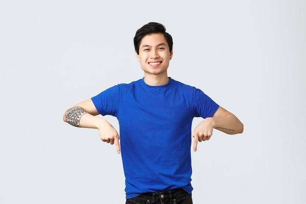 Verschiedene emotionen, lebensstil und werbekonzept der menschen. hübscher fröhlicher lächelnder asiatischer mann im blauen t-shirt, das finger nach unten zeigt. attraktiver männlicher student verkünden nachrichten und zeigen fahne.