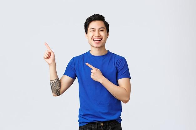 Verschiedene emotionen, lebensstil und werbekonzept der menschen. hübscher sorgloser asiatischer mann in blauem t-shirt, zeigefinger obere linke ecke und erfreut lächeln, gute neue promo einführen, banner zeigen