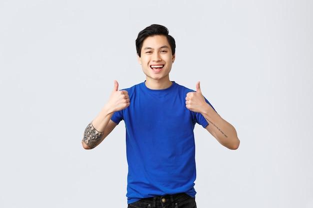 Verschiedene emotionen, lebensstil und werbekonzept der menschen. optisch gutaussehender asiatischer mann im blauen t-shirt, der unterstützend daumen hoch zeigt, um das produkt zu empfehlen oder zu garantieren.