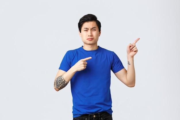 Verschiedene emotionen, lebensstil und werbekonzept der menschen. unzufriedener und trauriger asiatischer mann im blauen t-shirt, der mit den fingern nach rechts zeigt, schluchzt und jammert, sich über eifersüchtige und störende situation beschwert