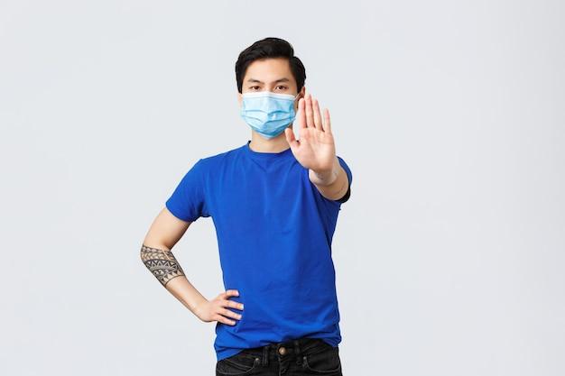 Verschiedene emotionen, soziale distanzierung, selbstquarantäne bei covid-19 und lifestyle-konzept. ernster asiatischer mann in medizinischer maske sagt stopp, zeige palme in verbot oder einschränkung betrete ohne schutz