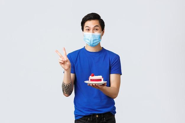 Verschiedene emotionen, soziale distanzierung, selbstquarantäne bei covid-19 und lifestyle-konzept. hübscher glücklicher asiatischer kerl in medizinischer maske, der zu hause zum mitnehmen isst, kuchen hält und friedenszeichen zeigt