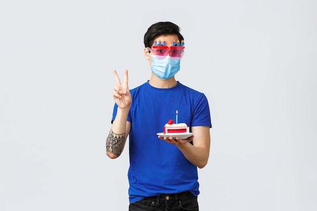 Verschiedene emotionen, soziale distanzierung, selbstquarantäne bei covid-19 und lifestyle-konzept. süßer b-day-typ bestellt lieferkuchen zum geburtstag, zeigt friedenszeichen, trägt eine lustige brille