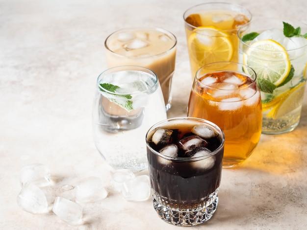 Verschiedene erfrischende getränke in gläsern mit eis