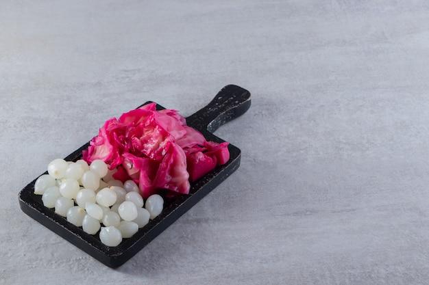 Verschiedene essiggurken gemüse auf einem steintisch platziert.