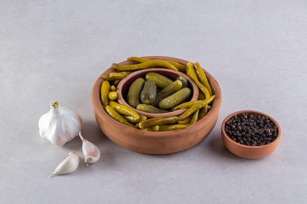 Verschiedene essiggurken gemüse auf einer steinoberfläche platziert.
