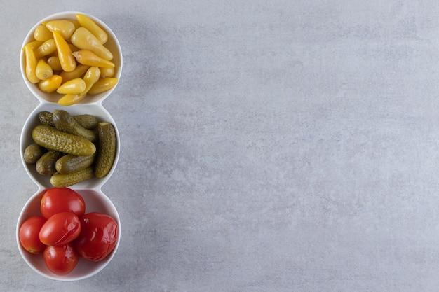 Verschiedene essiggurken gemüse in drei weißen schalen.