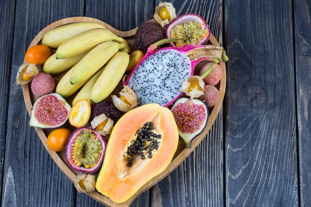 Verschiedene exotische früchte in einer herzförmigen holzplatte