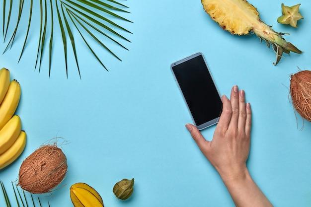 Verschiedene exotische früchte und ein palmblatt mit handy