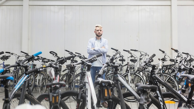 Verschiedene fahrräder, die den männlichen mechaniker steht in der werkstatt umgeben