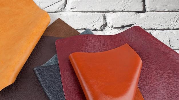 Verschiedene farben naturleder texturen muster auf weißem backstein hintergrund. mit kopierraum