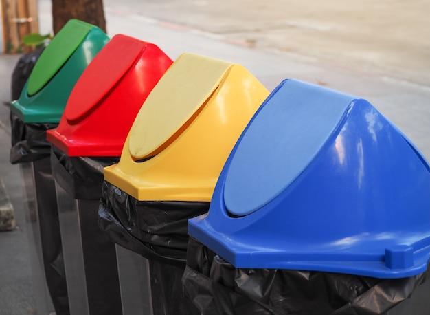 Verschiedene farbige bereiten mülleimereimer im park auf. recycling müll für die umwelt