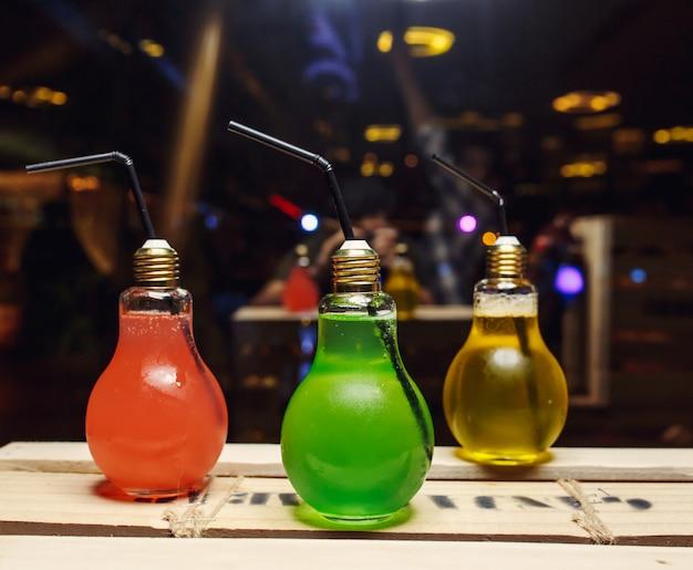 Verschiedene farbige cocktails in lampenflaschen