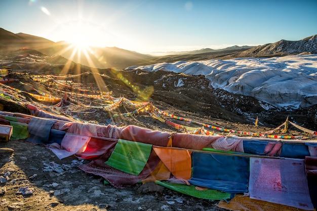 Verschiedene farbige flaggen am berg während des sonnenaufgangs