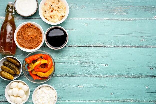 Verschiedene fermentierte lebensmittel wie gurken, sauerkraut, apfelessig, miso auf rustikalem minztisch. draufsicht und kopierraum. gesunde produkte für immunität und darm