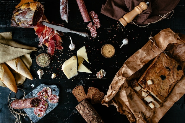 Verschiedene fleischdelikatessen: sticks von geräucherter salami, käse, gewürze, prosciutto
