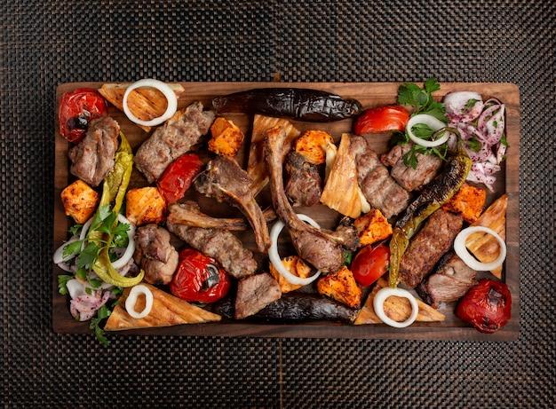 Verschiedene fleischspiesse mit zwiebeln, kräutern und gegrilltem gemüse