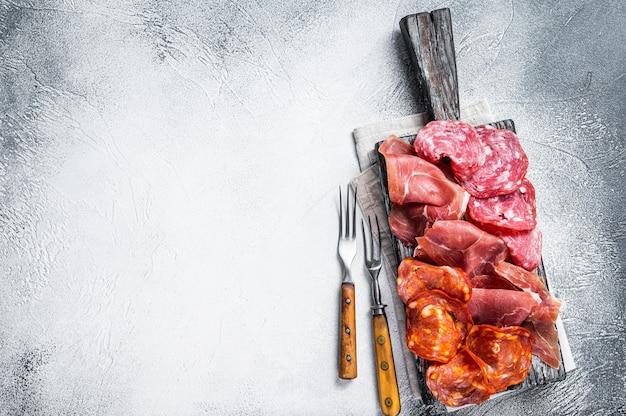 Verschiedene fleischvorspeisen - salami, jamon, choriso-würstchen. weißer hintergrund. ansicht von oben. platz kopieren.