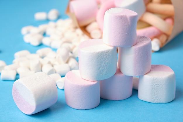 Verschiedene formen von marshmallows in papier eingewickelt auf blauem hintergrund, nahaufnahme, umweltfreundliche süßigkeitenverpackung, süße perkussion