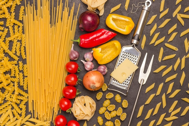 Verschiedene formen von trockenen nudeln mit gemüse tomaten, paprika. käse, reibe und gabel.