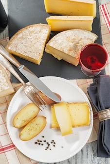 Verschiedene französische käsesorten mit einem glas wein
