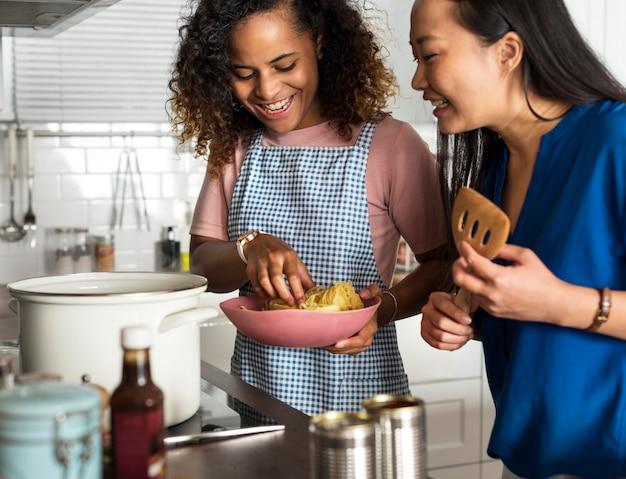 Verschiedene frauen, die zusammen in der küche kochen
