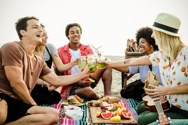 Verschiedene freunde, die ein strandpicknick genießen