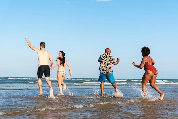 Verschiedene freunde, die spaß am strand haben