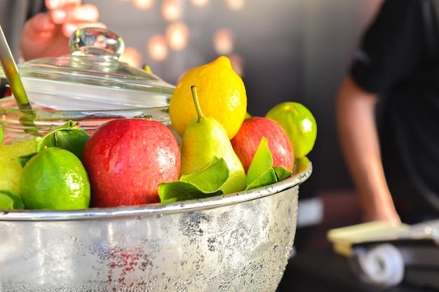 Verschiedene frische früchte und gemüse in stahlkorb gelbe zitronengrüne zitrone und roter apfel