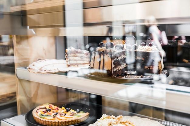Verschiedene frische kuchen in der fensteranzeige