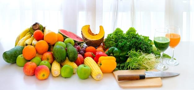 Verschiedene frische reife früchte und gemüse auf dem tisch mit weißem vorhanghintergrund