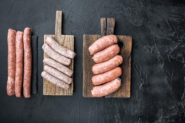 Verschiedene frische rohe wurstwaren aus schweinefleisch, rindfleisch und hühnchen, draufsicht, auf schwarzem tisch