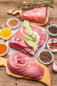 Verschiedene frische schweinefleischstücke sortiert. rohes fleisch mit gewürzen. filet, schulterblatt, nacken