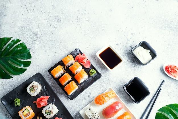 Verschiedene frische und köstliche sushi auf schwarz-weißem schiefer mit metall- und schieferstäbchen, sauce und grünen blättern auf heller steinoberfläche