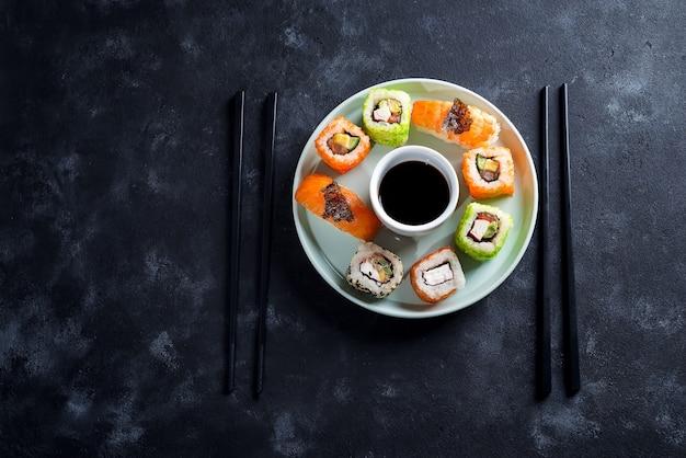 Verschiedene frische und köstliche sushi stellten auf keramische platte mit schieferstöcken, soße auf schwarzem steinhintergrund ein